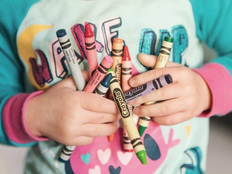 kindergartener holding crayons